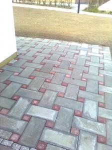 Belægning i grå betonfliser 20x40cm, med rød kopsten.