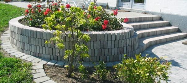 Rund støttemur i farvede holmegaardsfliser.