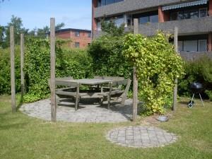 Terrasse udført i holmegaardsfliser, omkranset af espaliere.