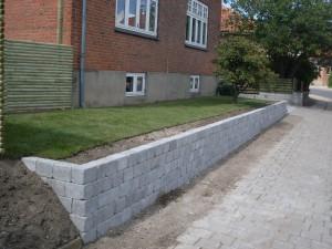 Støttemur i grå holmegaardsblokke, rullegræs på forstykket imellem hus og støttemuren.