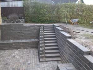 Støttemur af 'Lock Blok XL', trappe af betonelementer og terrasse udført i Holmegaardssten. Begge dele etableret under terræn med dræn.
